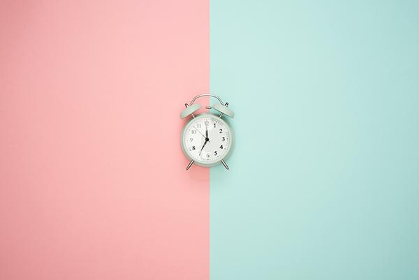 Klok op roze en groene achtergrond